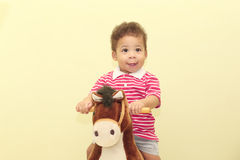 Portrait of an adorable african boy in his horse toy. Stock Photos