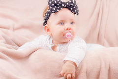 Portrait of adorable baby. Portrait of a beautiful baby girl with the black band on her head and a binky lying on the sofa Royalty Free Stock Images