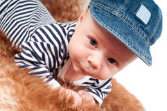 Portrait of adorable baby in cap lying on fur Royalty Free Stock Image