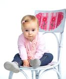 Portrait of an adorable baby girl. Wearing a pink with pearl necklace sitting on a c Stock Photography