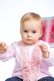 Portrait of an adorable baby girl. Wearing a pink with pearl necklace sitting on a c Royalty Free Stock Image