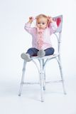 Portrait of an adorable baby girl. Wearing a pink with pearl necklace sitting on a c Stock Image