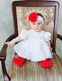 Portrait of an adorable baby girl. Portrait of a beautiful baby girl in white dress wearing red flower trendy headband Stock Photo