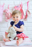 Portrait of an adorable baby girl. Portrait of a cute little smiling girl with baby clothes hanging on background Royalty Free Stock Photos