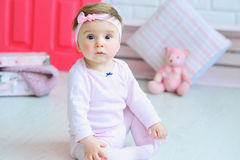 Portrait of an adorable baby girl. Cute little girl wearing pink clothes and trendy headband with a bow Stock Photos