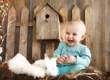 Portrait of an adorable baby girl and little white rabbit. Easte. Portrait of an adorable baby girl and little white rabbit near the wooden background. Easter Royalty Free Stock Photography