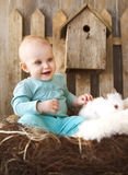 Portrait of an adorable baby girl and little white rabbit. Easte. Portrait of an adorable baby girl and little white rabbit near the wooden background. Easter Royalty Free Stock Photos
