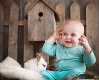 Portrait of an adorable baby girl and little white rabbit. Near the wooden background. Easter concept Royalty Free Stock Images