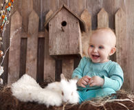 Portrait of an adorable baby girl and little white rabbit. Near the wooden background. Easter concept Stock Photos