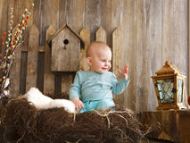 Portrait of an adorable baby girl near the wooden background. Easter concept Stock Image