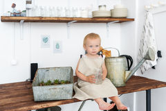 Portrait of adorable baby girl playing with domestic plants and potted sprouts.  Royalty Free Stock Image