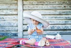 Portrait of an adorable baby girl playing, sitting wearing a straw hat.  Royalty Free Stock Images