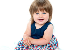 Portrait of an adorable baby girl sitting up. Wearing a beautoful blue dress Stock Photography