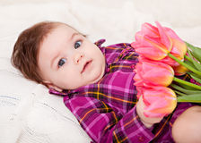 Portrait adorable baby girl. With spring flowers Stock Image
