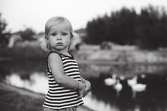 Portrait of adorable baby girl. Standing near lake, monochrome Stock Photography