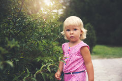 Portrait of adorable baby girl. Standing near plant Royalty Free Stock Photography
