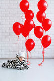 Portrait of an adorable baby girl. Adorable baby wearing cute striped costume and red balloons Royalty Free Stock Image