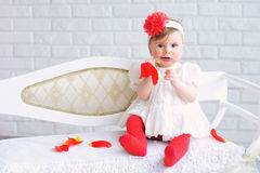 Portrait of an adorable baby girl. Adorable baby girl in white and red with trendy headband playing with tulip flower Stock Photo