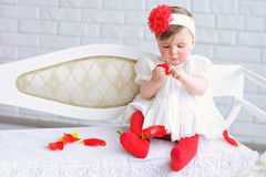 Portrait of an adorable baby girl. Adorable baby girl in white and red with trendy headband playing with tulip flower Royalty Free Stock Photo