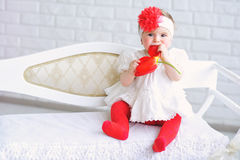 Portrait of an adorable baby girl. Adorable baby girl in white and red with trendy headband playing with tulip flower Stock Image