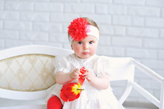 Portrait of an adorable baby girl. Adorable baby girl in white and red with trendy headband playing with tulip flower Royalty Free Stock Photos