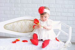 Portrait of an adorable baby girl. Adorable baby girl in white and red with trendy headband playing with tulip flower Stock Photography