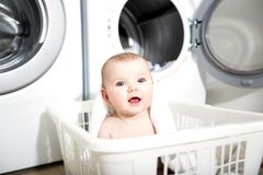 Portrait of an adorable baby sitting in a laundry basket Stock Photos