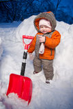 Portrait of adorable baby stay near snow shovel Royalty Free Stock Photos