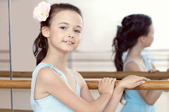 Portrait of adorable ballerina posing with barre Stock Photo