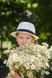 Portrait adorable boy in a hat with big white bouquet of camomiles Royalty Free Stock Photography