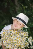 Portrait adorable boy in a hat with big white bouquet of camomiles Stock Photo