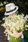 Portrait adorable boy in a hat with big white bouquet of camomiles Stock Photos