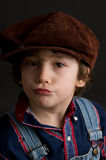 Portrait of an adorable boy wearing a cap. Little boy wearing an old fashioned cap looking at the camera with a funny expression Royalty Free Stock Images