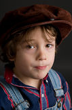 Portrait of an adorable boy wearing a cap. Little boy wearing an old fashioned cap looking at the camera with a serious expression Stock Image