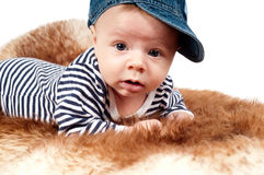 Portrait of adorable child in hat lying on fur Stock Photo