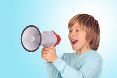 Portrait of adorable child with a megaphone. Isolated on a over blue background Stock Photos