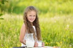 Portrait of adorable curly girl drinking a glass milk outdoor summer. Little cute girl drinking a glass of milk in garden. Adorable curly kid having breakfast Stock Photography