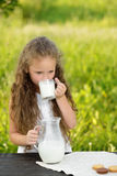Portrait adorable curly girl drinking a glass of milk outdoor summer. Little cute girl drinking a glass of milk in garden. Adorable curly kid having breakfast Stock Photography