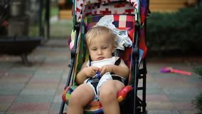 Portrait of adorable cute caucasian blond toddler boy sitting bright multicolored stroller and being rocked by mother. During walk at backyard outdoors stock footage