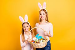 Portrait of adorable cute gentle beautiful sensible careless dreamy family holding together one whisker basket with handmade pain. Ted chocolate eggs isolated on royalty free stock photography