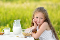 Portrait of adorable girl having breakfast and drinking milk outdoor. Cereal, healthy lifestyle. Smiling little girl sitting near the table and having breakfast Stock Images