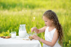 Portrait of adorable girl having breakfast and drinking milk outdoor. Cereal, healthy lifestyle. Smiling little girl sitting near the table and having breakfast Stock Photo