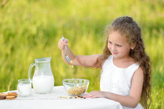 Portrait of adorable girl having breakfast and drinking milk outdoor. Cereal, healthy lifestyle. Smiling little girl sitting near the table and having breakfast Royalty Free Stock Photos