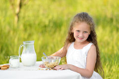 Portrait of adorable girl having breakfast and drinking milk outdoor. Cereal, healthy lifestyle. Smiling little girl sitting near the table and having breakfast Stock Image