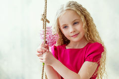 Portrait of an adorable girl with pink flowers Stock Photos
