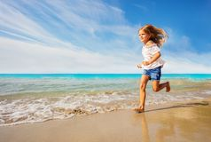Adorable girl running along sandy beach in summer stock images