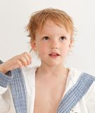 Portrait of adorable happy boy. In dressing gown after bath. Over grey Royalty Free Stock Image