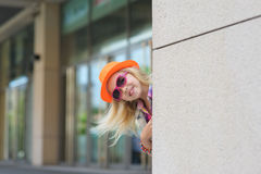 Portrait of adorable happy child. Adorable happy child in sunglasses and orange hat. Shop windows in the background. Girl peeking around the corner. Blond hair Stock Image