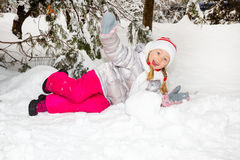 Portrait of adorable happy little girl grinning happily at the camera on a sunny winter`s day Royalty Free Stock Photo