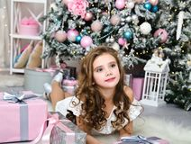 Portrait of adorable happy smiling little girl child in princess dress with gift boxes lying near fir tree. In christmas time stock photo